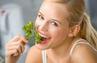 Young happy smiling woman eating at kitchen