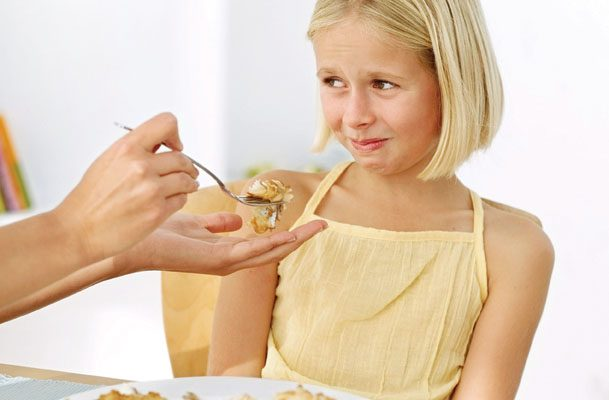 Mother's Hand Feeding Food to a Young Girl (13-14) Who Is Making a Face --- Image by © Royalty-Free/Corbis