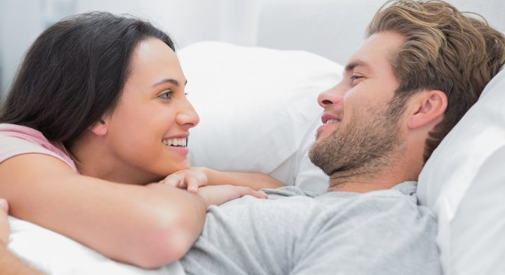 Cheerful couple awaking and looking at each other in bed