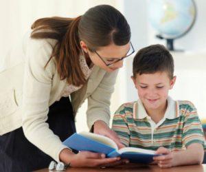 Teacher helping boy (8-9) with work in classroom