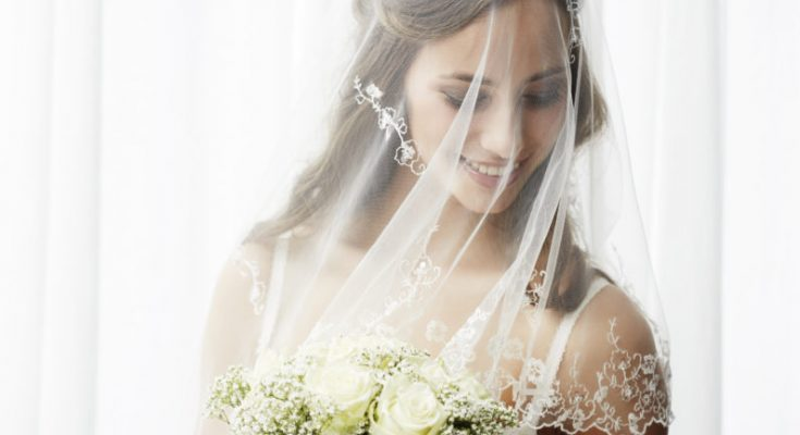 Excited young bride in veil holding bouquet