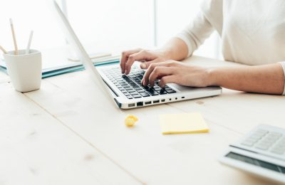 Woman sitting at desk and working at computer hands close up