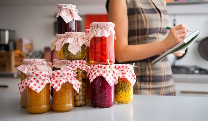 In the foreground, a stack of glass jars filled with home-made preserved vegetables. In the background, the profile of a woman listing the different ingredients before she stores them away for winter.