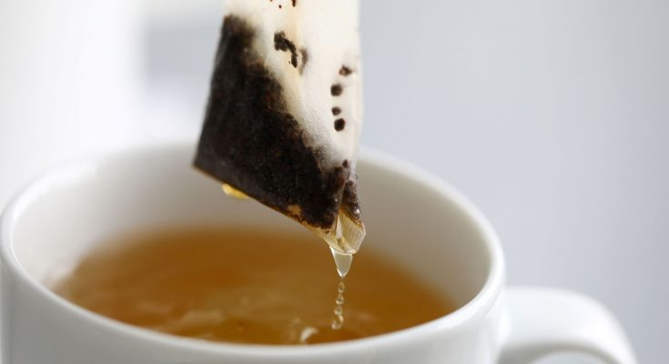 Hot water trickling down from herbal potion teabag close-up