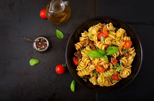 Pasta Fusilli  with tomatoes, beef and basil in black bowl on table. Top view. Flat lay